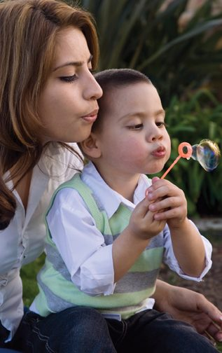 A young mother blowing bubbles with her little boy.